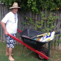 A picture of a man holding a wheel barrow